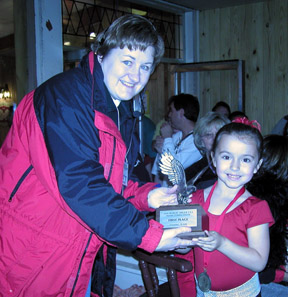 Shawnda and young skater are holding the eagle trophy