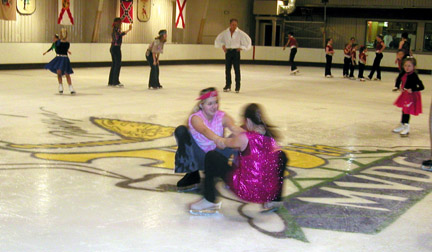 fun on ice, two skaters are doing a low spin