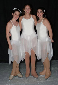 Three skaters in snowflake costumes