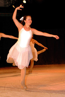 One skater poses as a snowflake in an arabesque