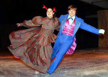 A waltzing couple linked by arms.  The woman has one foot out to the side.  Both skaters have their outside arms extended