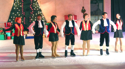 Adult skaters taking their bows in a line, linked together by holding their hands