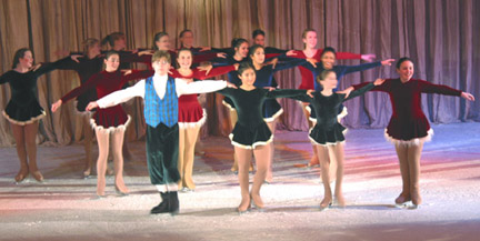 Three lines of skaters dressed as carolers with their arms oustretched and touching each other's shoulder