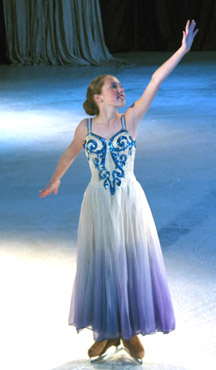 One skater dressed as an ice crystal posing with her arm above her head