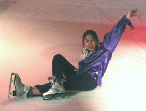 A jester sitting down on the ice posed with her arm above her head
