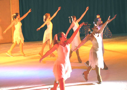 Several snowflake skaters posing in a semi circle, with their arms reaching above their head