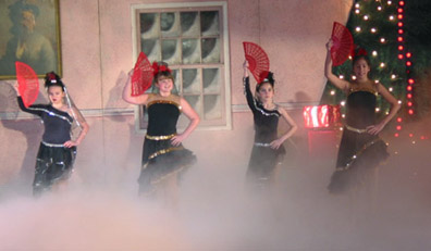 Four spanish dancers starting the number with their fans in front of their faces, with a cloud of smoke at their feet