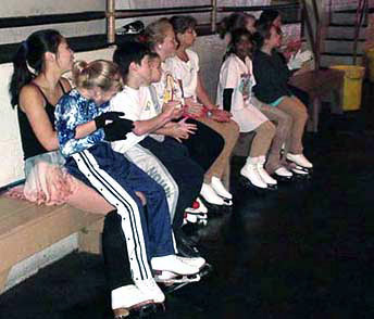 Skaters seated and watching from the bench
